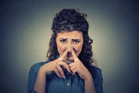 Woman pinches nose with fingers looks with disgust something stinks bad smell