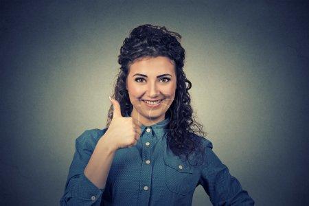 Photo pour Belle femme d'affaires souriante isolée sur fond de mur gris. Pouce en l'air . - image libre de droit