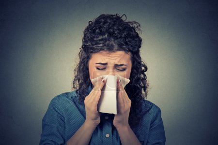 Photo pour Gros plan portrait femme éternuement dans un tissu soufflant son nez qui coule - image libre de droit
