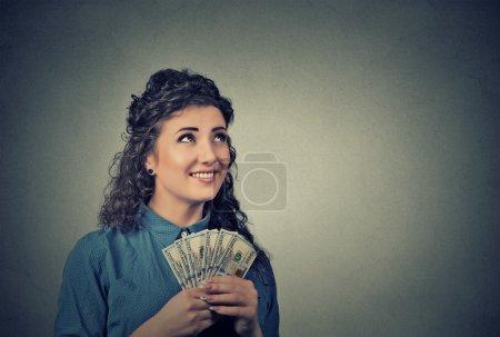 Photo pour Closeup portrait heureux heureux femme jeune entreprise détient une somme billets d'un dollar dans la main en levant fond isolé mur gris. Sentiment d'expression faciale des émotions positives. Récompense financière - image libre de droit