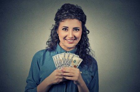 Photo pour Closeup portrait heureux heureux succès jeune fortunée détient une somme billets d'un dollar dans la main isolés sur fond de mur gris. Sentiment d'expression faciale des émotions positives. Récompense financière - image libre de droit