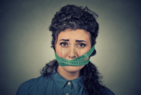Diet restriction and stress concept. Frustrated woman with measuring tape around her mouth