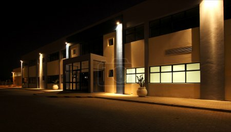 Photo for External view of a modern building at night with security floodlights burning - Royalty Free Image