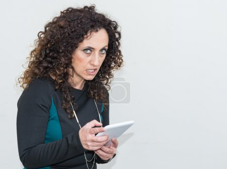 Modern mature woman, angry, using the tablet.