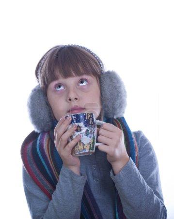 Photo pour Teen girl en gris chaud casque avec coupe de Noël décoré en blanc de thé isolé mains boissons - image libre de droit