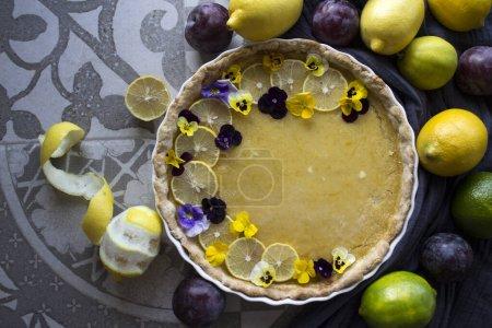 Photo pour Tarte au citron décorée de tranches de citron et de fleurs sauvages. Classique dessert tarte vue de dessus photo. - image libre de droit