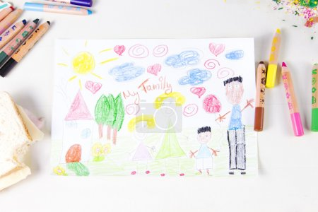 Kids drawing of multi-racial Family and colored pencils on woode