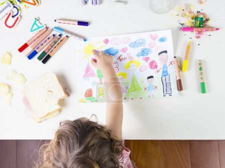 Little girl point at a sun in a kids drawing of multi-racial Fam