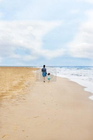 Authentic photo about mother and daughter walking on the beach with footprints