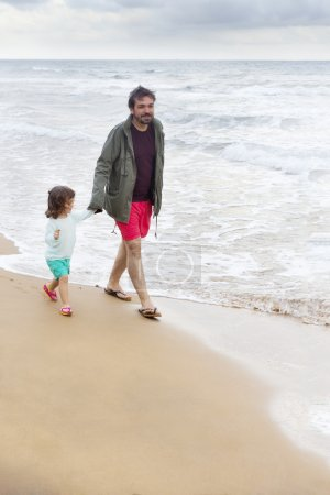 Authentic photo about father and daughter walking on the beach with footprints