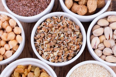 Photo for Bowls of various legumes and seeds. Lentils, sesame seeds, pistachio nuts, flaxseed, raisins, peanuts and chickpeas.   Sprouted legumes. Wooden background - Royalty Free Image