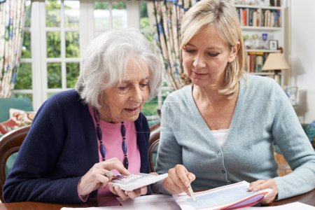 Mature Woman Helping Senior Neighbor With Home Fin...