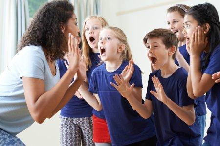 Photo pour Groupe d'enfants avec professeur appréciant la classe de théâtre ensemble - image libre de droit
