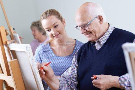 Seniors Attending Painting Class With Teacher