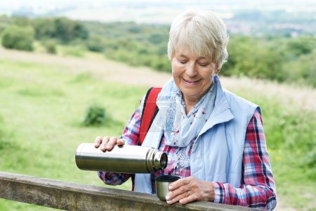 Senior Woman Having Drink From Flask Whilst On Walk