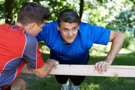 Mature Man Exercising With Personal Trainer In Park