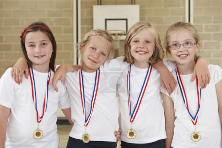 Female School Sports Team In Gym With Medals