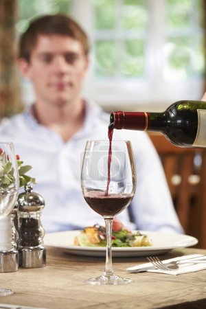 Waitress Pouring Customer Glass Of Red Wine