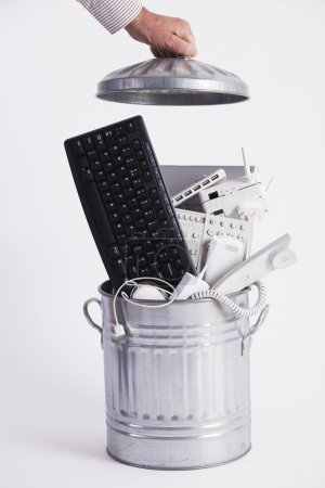 Photo for Businessman Filling Garbage Can With Obsolete Office Equipment - Royalty Free Image