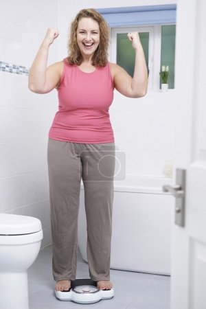 Happy Woman Weighing Herself On Scales In Bathroom