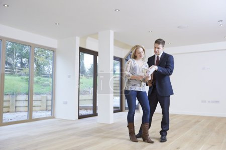 Agent immobilier montrant potentiel acheteur féminin autour de la propriété