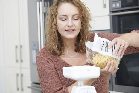 Plus Size Woman On Diet Weighing Out Pasta For Meal