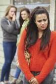 Unglückliche Teenager-Mädchen wird geplaudert über von Kollegen