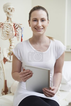 Portrait Of Female Osteopath In Consulting Room With Digital Tab
