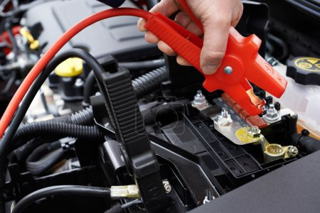 Photo for Close-Up Of Mechanic Attaching Jumper Cables To Car Battery - Royalty Free Image