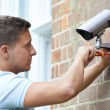 Security Consultant Fitting Security Camera To Hou...
