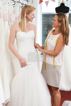 Bride Being Fitted For Wedding Dress By Store Owner