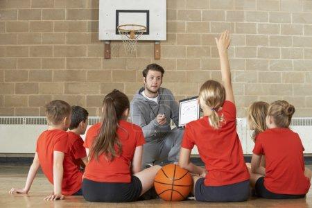 Coach Giving Team Talk To Elementary School Basketball Team