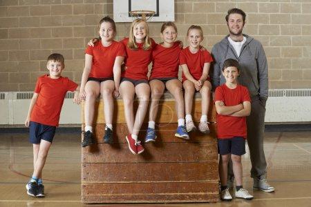 Photo pour Portrait De L'équipe De Gym De L'école Assis Sur Le Cheval Vaulting - image libre de droit