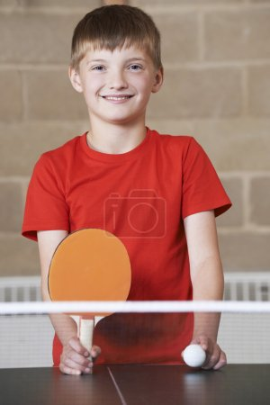 Portrait Of Boy Playing Table Tennis In School Gym
