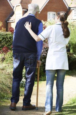 Carer Helping Senior Man To Walk In Garden Using Walking Stick