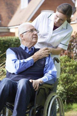 Carer Pushing Senior Man In Wheelchair...