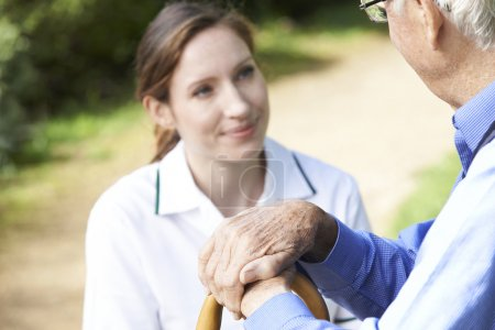 Senior Man's Hands Resting On Walking Stick With Care Worker In