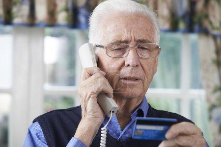 Foto de Senior hombre dando detalles de tarjeta de crédito en el teléfono - Imagen libre de derechos