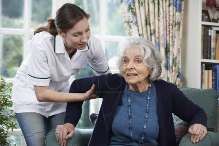Care Worker Helping Senior Woman To Get Up Out Of Chair