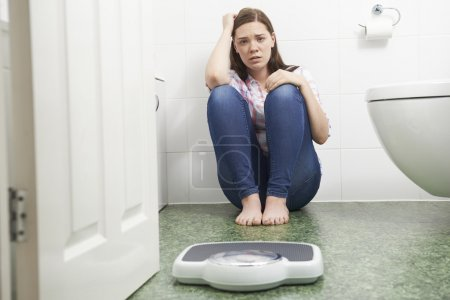 Photo for Unhappy Teenage Girl Sitting On Floor Looking At Bathroom Scales - Royalty Free Image
