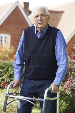 Senior Man In Garden Using Walking Frame