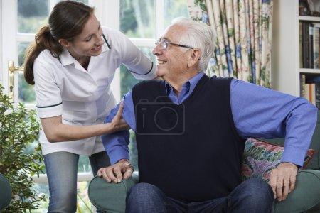 Photo pour Travailleur de soins aidant l'homme âgé à se lever de la chaise - image libre de droit