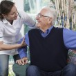 Care Worker Helping Senior Man To Get Up Out Of Ch...