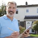 Builder Preparing Estimate For Exterior Home Impro...