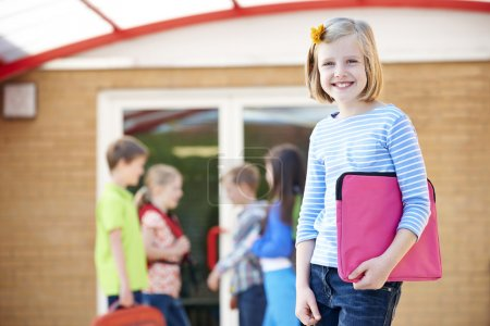 Photo for Girl Standing Outside School With Book Bag - Royalty Free Image