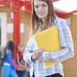Portrait Of Teacher Standing In Playground With Fo...