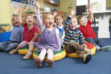 Photo for Group Of Pre School Children Answering Question In Classroom - Royalty Free Image
