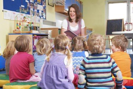 Foto de Grupo de niños de preescolar, escuchar al maestro leer historia - Imagen libre de derechos