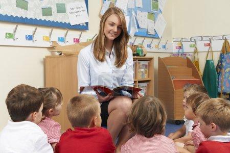 Foto de Libro de lectura de profesor a la clase de la escuela primaria - Imagen libre de derechos