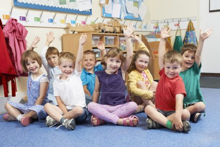 Group Of Elementary School Pupils Putting Hands Up In Class